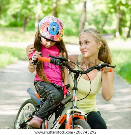 young mother calms the sad daughter who did not get to ride a bike - stock photo