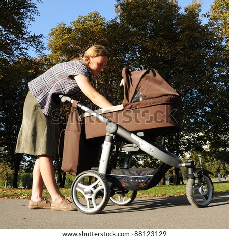 Young mother cares about baby in stroller in the park - stock photo