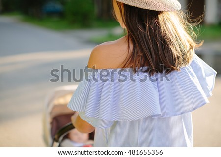 young mother carries a child in a stroller