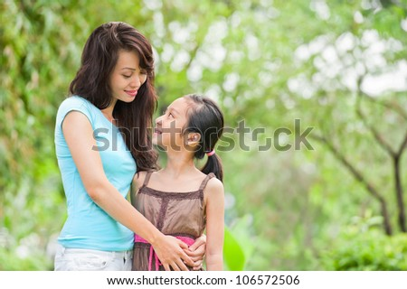 Young mother embracing her daughter outside - stock photo