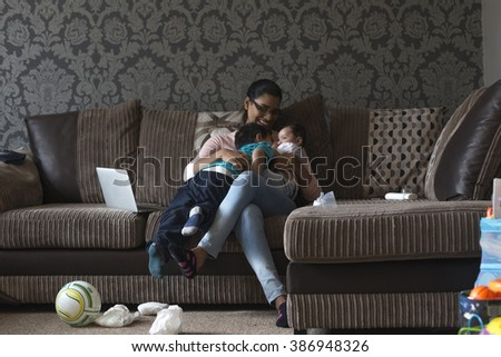 Young mother enjoying a cuddle with her two sons.She has the baby in her arms, who's brother is snuggling in to him.  - stock photo