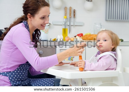 young mother feeding baby with a spoon in the kitchen at home - stock photo