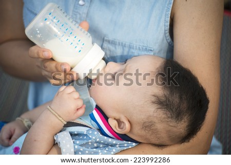 Young mother feeding her baby girl with milk bottle on bedroom - stock photo