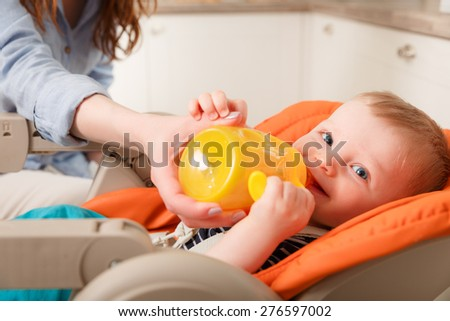 young mother feeding her baby with a bottle - stock photo