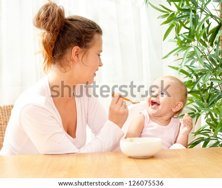 young mother feeding her baby with a spoon - stock photo