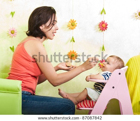 Young mother feeding her little baby son - stock photo