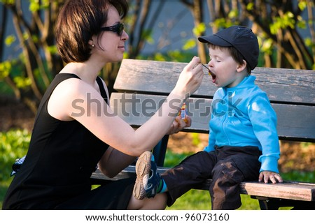Young mother feeding her little baby son outdoors in city park - stock photo