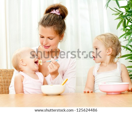 young mother feeding her two daughters from a spoon - stock photo