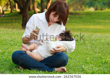 young mother feeding milk the infant baby and using smartphone in park - stock photo