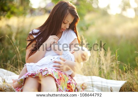 young mother feeding milk the infant baby outdoors - stock photo