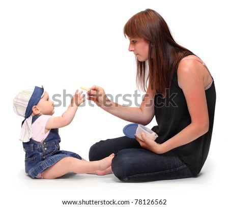 Young mother feeds her baby. Studio shot on a white background. - stock photo