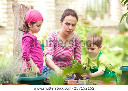 Young mother gardening in front or back yard with her children helping her - stock photo