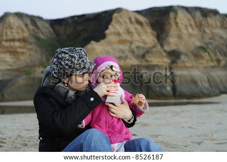 Young mother gives milk to her baby daughter on the beach just after sunset. Lit by natural available light only - no flash. - stock photo