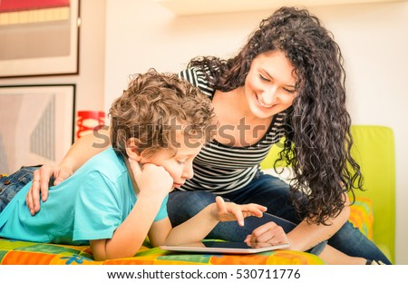 Young mother having fun with son using tablet on bed - Learning computer tech with sister in children room - Teacher showing boy how to interact on modern device - Vivid filter with focus on kid face