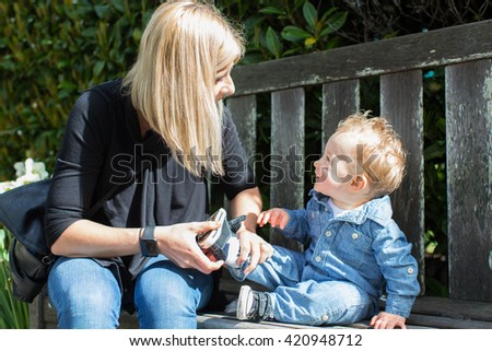 young mother helping her cute toddler boy putting his shoe on enjoying time together in the park - stock photo