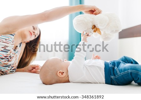 Young mother holding a teddy bear in hand and baby boy playing with it  - stock photo