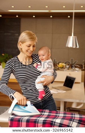 Young mother holding baby while ironing, smiling happy. - stock photo