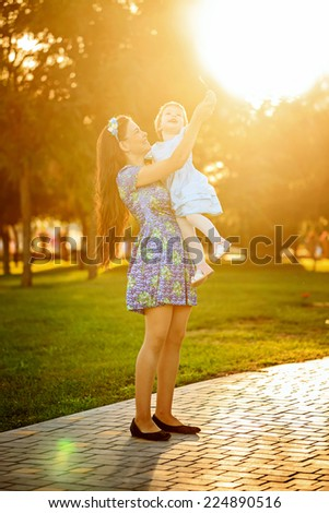 Young mother holding daughter in her arms a city park - stock photo