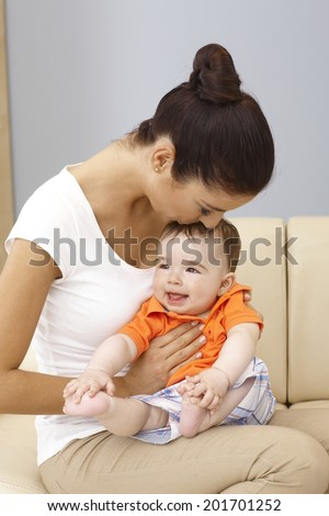 Young mother holding happy baby boy in lap, kissing head. - stock photo