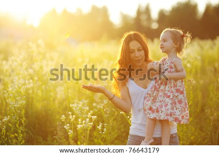 Young mother holding her adorable toddler girl at sunset - stock photo