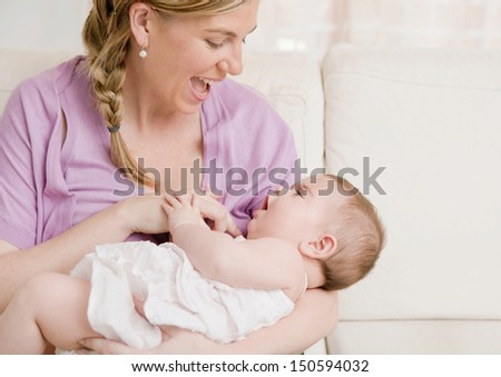 Young mother holding her baby girl in her arms and playing with her while sitting on a white sofa at home, enjoying motherhood and having fun. - stock photo