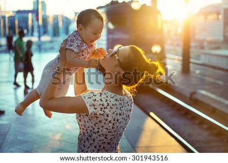 Young mother holding her baby on a train station - stock photo
