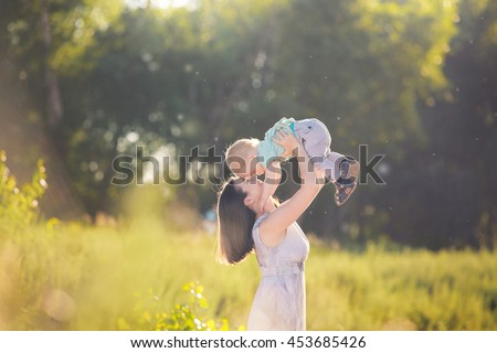 Young mother holding her Cute little toddler boy. Adorable child having fun with his mom in the park on sunny summer day. Happy family with baby on sunset. Childhood, motherhood, family concept - stock photo