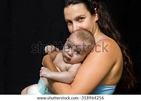 Young mother holding her little newborn baby on a black background - stock photo