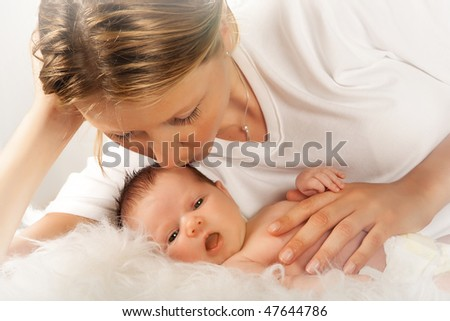 Young mother holding her twenty days old newborn baby - stock photo