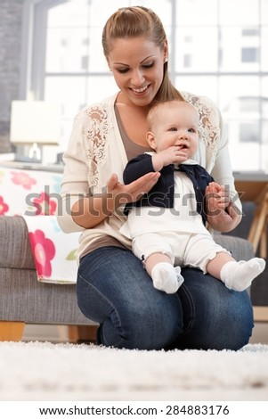 Young mother holding on lap baby daughter, kneeling on floor, smiling.