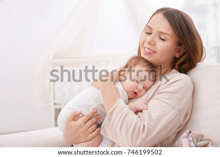 Young mother holding sleeping baby at home