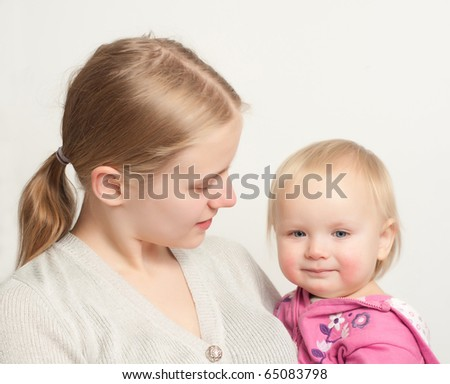 young mother holding  toddler daughter in pink