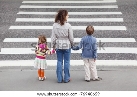 young mother holds hand of his little daughter and son and standing near cross road, behind - stock photo