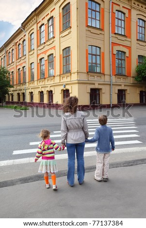 young mother holds hand of little daughter and son and crossing road, behind, yellow house, trees - stock photo
