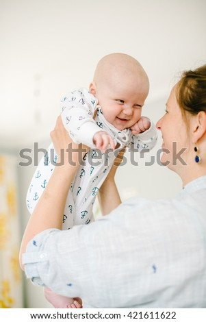 Young mother holds on hands of his young son at home. Mom happy. Child happy and laughing. The concept of family - stock photo