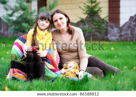 Young mother hug little daughter sitting on the green lawn