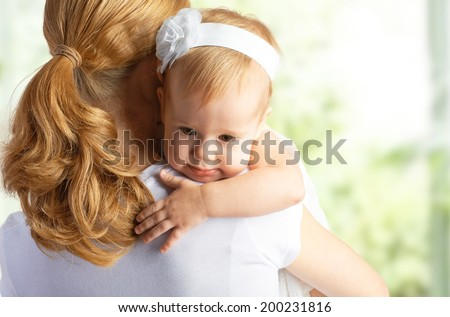 young mother hugging and comforting her baby daughter