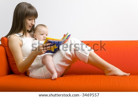 Young mother hugging baby boy. Sitting on orange couch. Reading to him book. Whole bodys. Side view