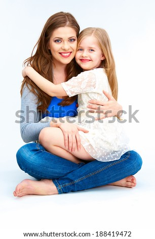 Young mother hugging daughter sitting on a floor. Isolated studio. - stock photo