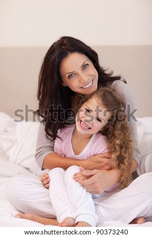 Young mother hugging her daughter