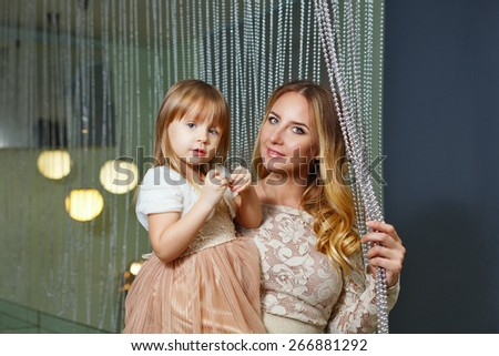 Young mother hugging her daughter tenderly. Mother holds daughter on hands. The concept of family happiness. - stock photo
