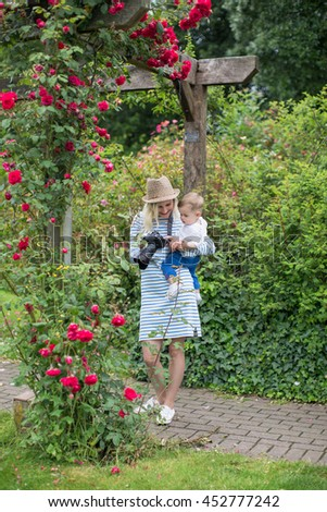 Young mother in a hat holding son on the hands and taking pictures in the park flowers - stock photo