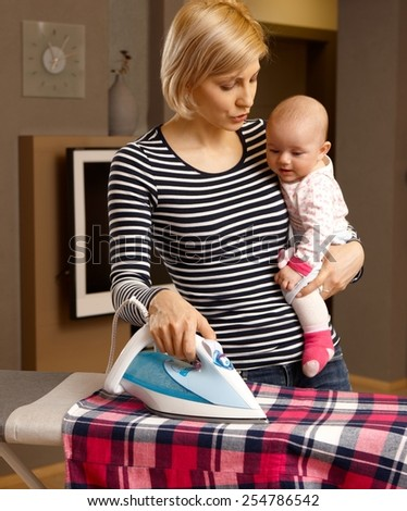 Young mother ironing while holding baby girl in arm. - stock photo
