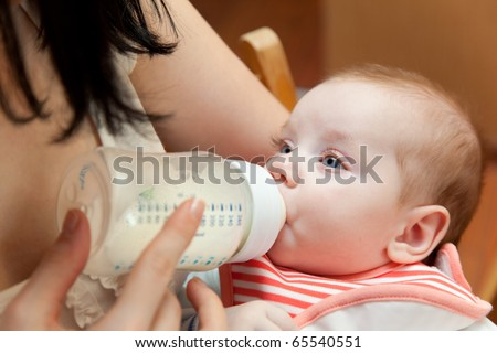 Young mother is feeding her baby from a bottleat home