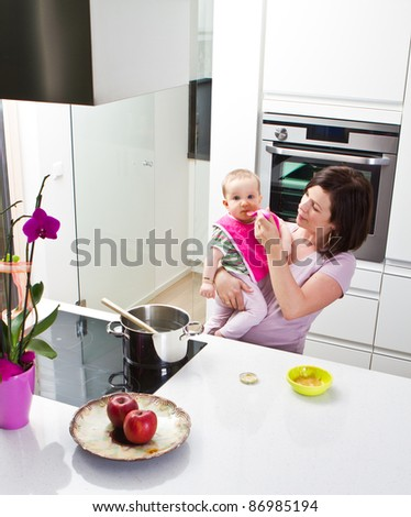 Young mother is feeding her baby in a modern kitchen setting. - stock photo