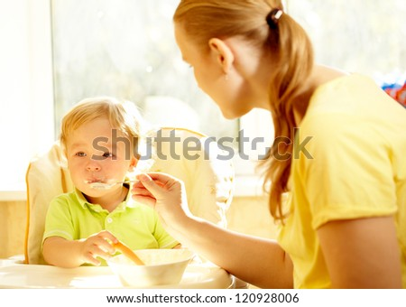 Young mother is feeding her two year old boy with porridge. - stock photo