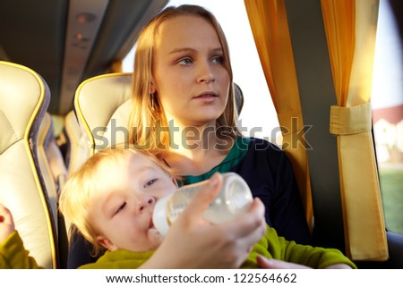 Young mother is feeding her two year old son with milk, while they are travelling by intercity bus. Close up portraits.