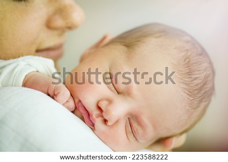 Young mother is holding her cute newborn baby girl - stock photo