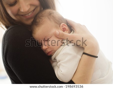 Young mother is holding her little baby - stock photo