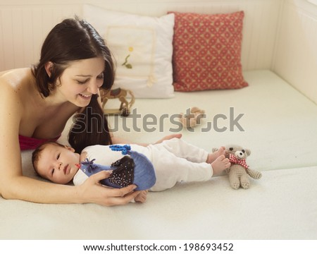 Young mother is playing with her little baby